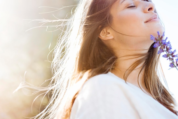 Vista lateral da mulher bonita posando com flor Foto gratuita