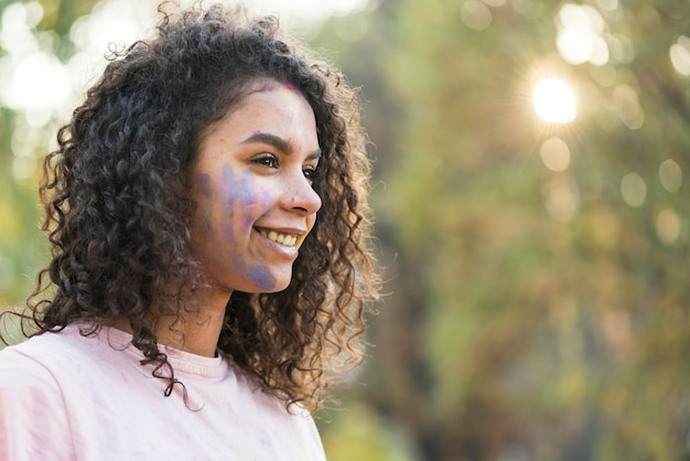 Vista lateral da mulher com tinta azul no rosto Foto gratuita