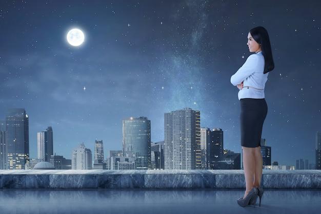 Vista lateral da mulher de negócios asiáticos em pé no terraço, olhando a paisagem urbana Foto Premium