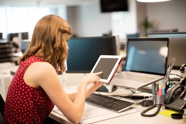 Vista lateral da mulher de negócios usando tablet digital no escritório Foto Premium