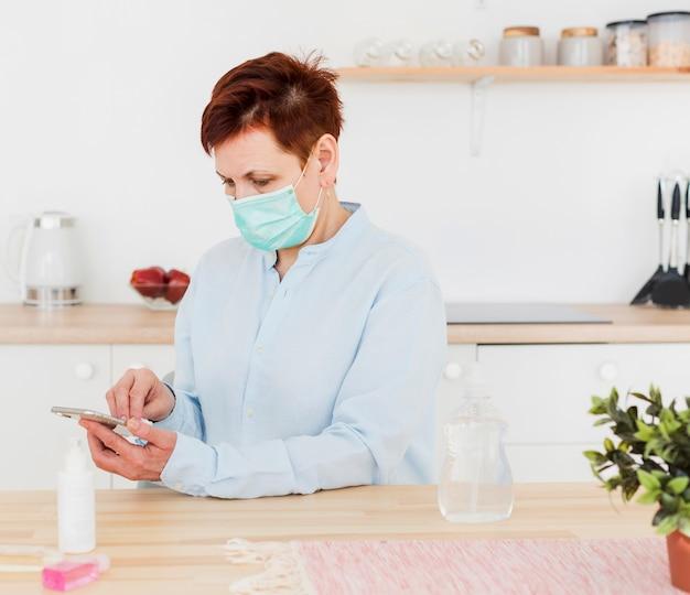 Vista lateral da mulher desinfetar o telefone enquanto usava máscara médica Foto Premium