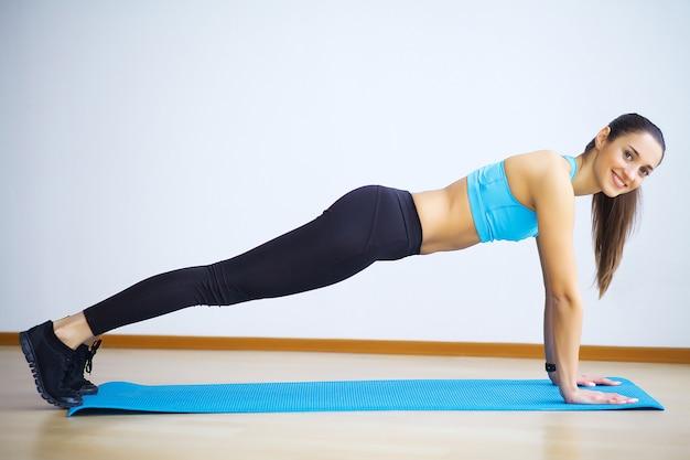Vista lateral da mulher do ajuste que faz prancha núcleo exercício. Foto Premium