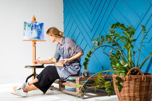 Vista lateral da mulher escrevendo e pintando Foto gratuita