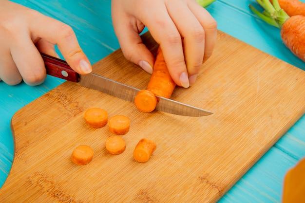 Vista lateral da mulher mãos corte cenoura na tábua com faca sobre fundo azul Foto gratuita
