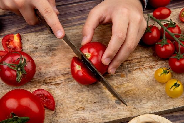 Vista lateral da mulher mãos tomate corte na tábua com faca na superfície de madeira Foto gratuita