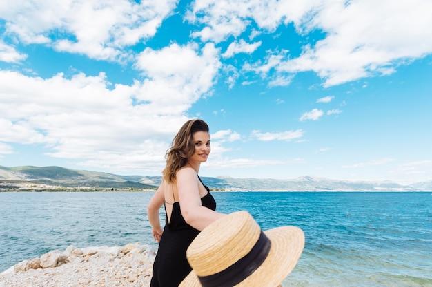 Vista lateral da mulher no oceano segurando o chapéu Foto gratuita