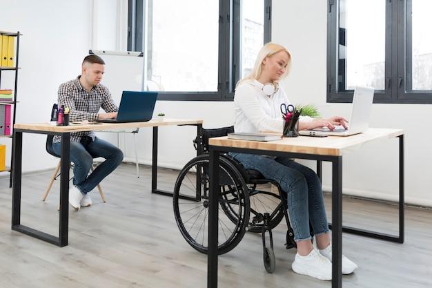 Vista lateral da mulher no trabalho de cadeira de rodas formar sua mesa Foto gratuita