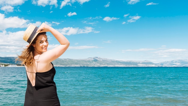Vista lateral da mulher posando no oceano Foto gratuita