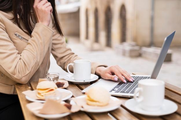 Vista lateral da mulher que trabalha ao ar livre e almoçar Foto gratuita