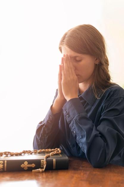 Vista lateral da mulher rezando com livro sagrado e rosário Foto Premium