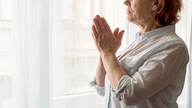 Vista lateral da mulher rezando Foto gratuita