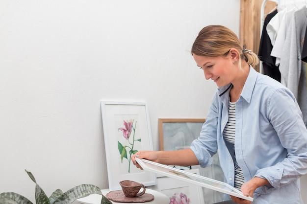 Vista lateral da mulher segurando a pintura de flores Foto gratuita