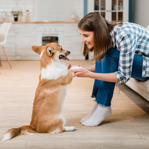 Vista lateral da mulher segurando as patas do seu cão Foto gratuita