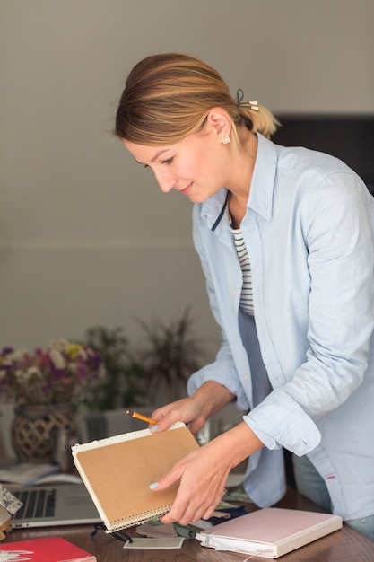 Vista lateral da mulher segurando o caderno e lápis Foto gratuita