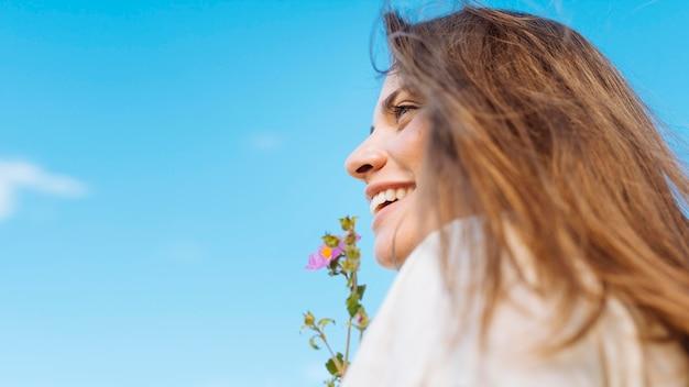 Vista lateral da mulher sorridente com cópia espaço e flor Foto gratuita