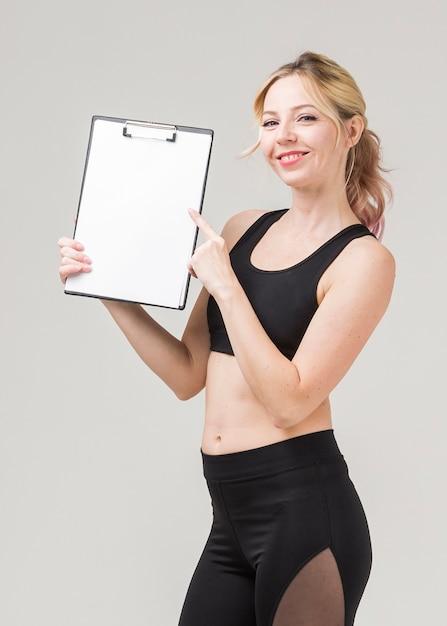Vista lateral da mulher sorridente em athleisure segurando o bloco de notas Foto gratuita