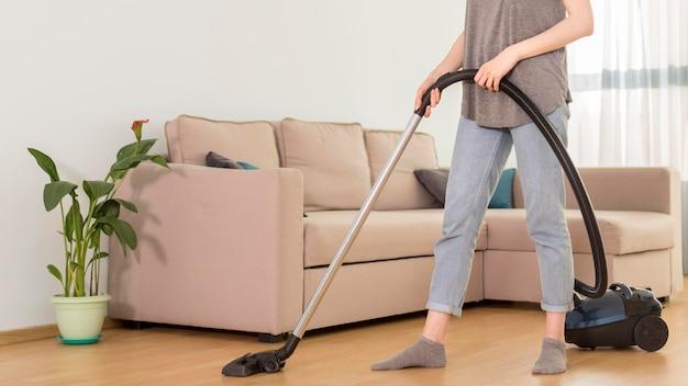 Vista lateral da mulher usando aspirador de pó no quarto Foto gratuita