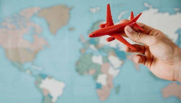 Vista lateral da pessoa segurando a estatueta do avião sobre o mapa Foto gratuita