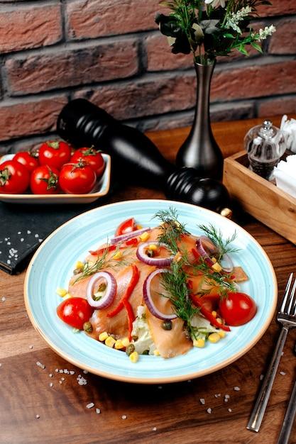 Vista lateral da salada de salmão com cebola roxa repolho e calos cobertos com endro no prato na mesa de madeira Foto gratuita