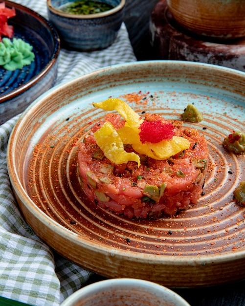Vista lateral da salada de salmão com molho de abacate e wasabi em um prato em tecido xadrez Foto gratuita