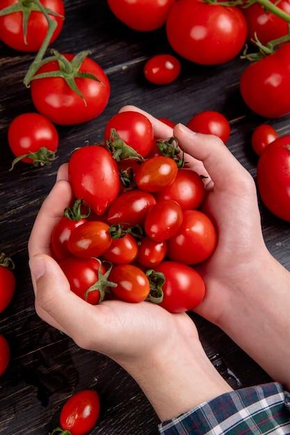 Vista lateral das mãos de mulher segurando tomates com outros na superfície de madeira Foto gratuita