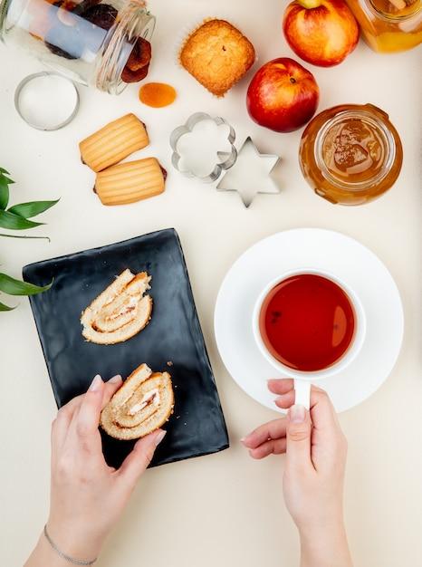 Vista lateral das mãos de mulher segurando uma fatia de rolo e xícara de chá com pêssegos pote de uvas passas compotas de cookies em branco Foto gratuita