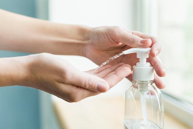 Vista lateral das mãos usando gel desinfetante para as mãos Foto gratuita