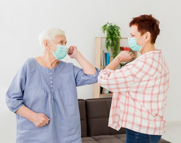 Vista lateral das mulheres mais velhas, cumprimentando-se em casa Foto gratuita