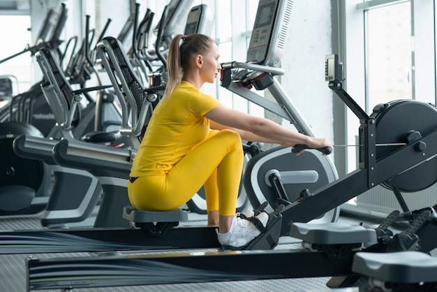 Vista lateral de ajuste jovens mulheres usando a máquina de remo no health club Foto Premium