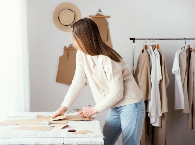Vista lateral de alfaiate feminina no estúdio com roupas Foto gratuita