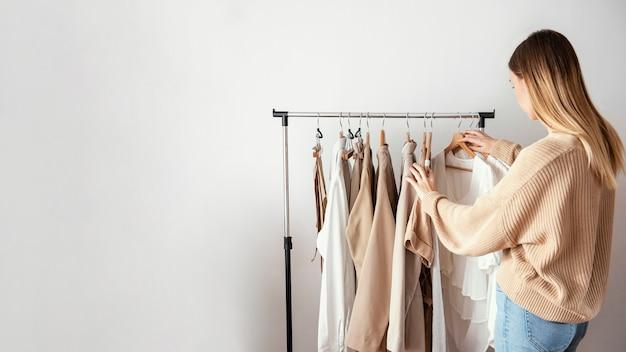 Vista lateral de alfaiate feminina verificando roupas em cabides com espaço de cópia Foto Premium
