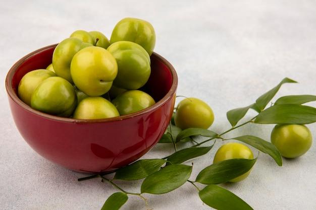 Vista lateral de ameixas verdes em uma tigela com folhas no fundo branco Foto gratuita