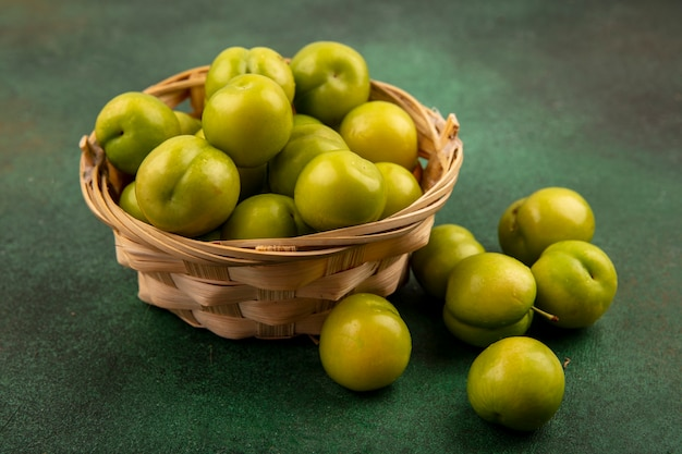 Vista lateral de ameixas verdes na cesta e sobre fundo verde Foto gratuita