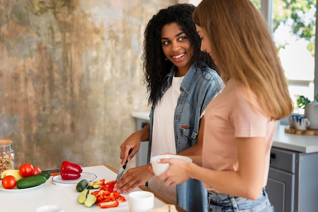Vista lateral de amigas cozinhando juntas na cozinha Foto gratuita