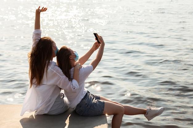 Vista lateral de amigos com máscaras médicas tirando selfie à beira do lago Foto gratuita