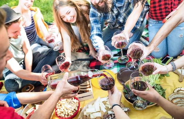 Vista lateral, de, amigos, servindo, e, brindar, vinho tinto, óculos Foto Premium