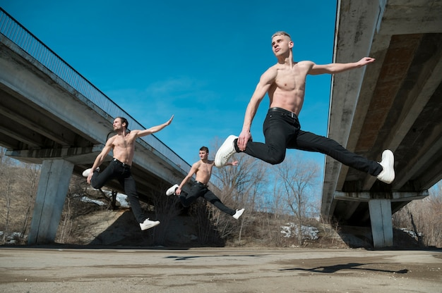 Vista lateral de artistas de hip hop sem camisa dançando no ar Foto gratuita
