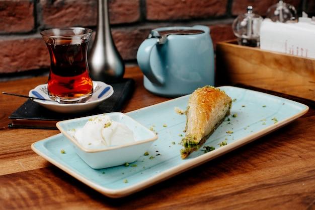 Vista lateral de baklava em forma triangular de doces turcos com pistache servido com sorvete no prato Foto gratuita