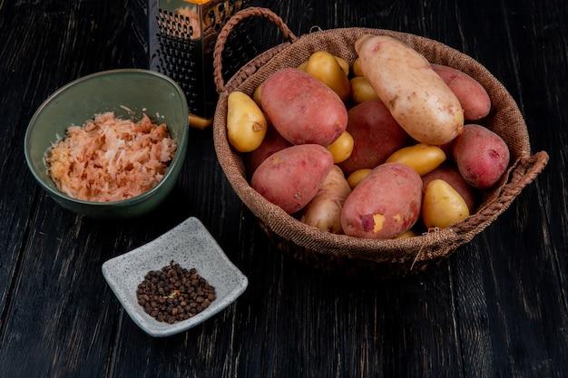 Vista lateral de batatas inteiras na cesta e as raladas na tigela com sementes de pimenta preta e ralador na mesa de madeira Foto gratuita