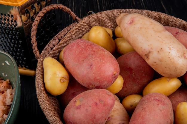 Vista lateral de batatas na cesta com ralador e batatas raladas em tigela na mesa de madeira Foto gratuita