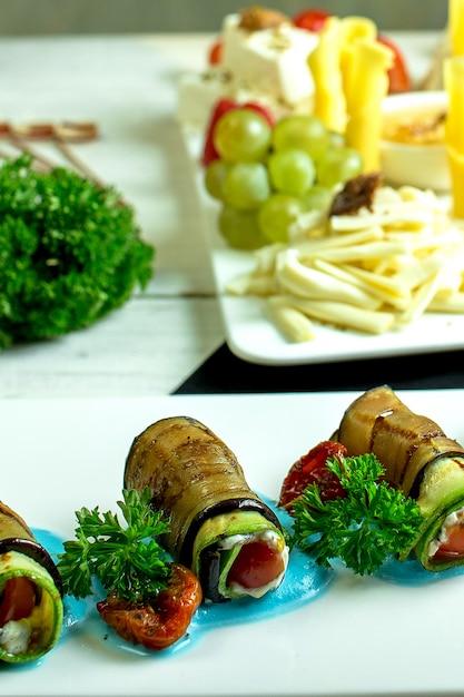 Vista lateral de berinjela frita rola com alho e creme de queijo no prato Foto gratuita