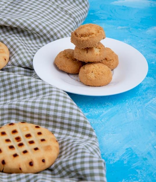 Vista lateral de biscoitos em um prato branco no azul Foto gratuita