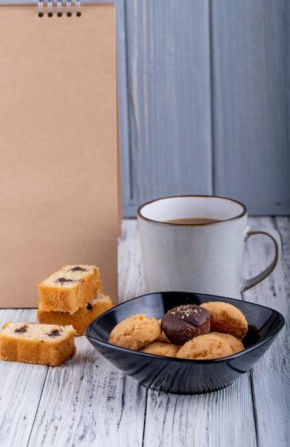 Vista lateral de biscoitos em uma tigela e uma xícara de chá no rústico Foto gratuita