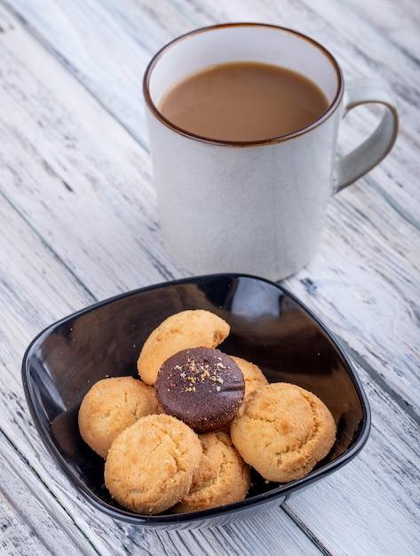 Vista lateral de biscoitos em uma tigela preta e um copo com cacau na madeira Foto gratuita