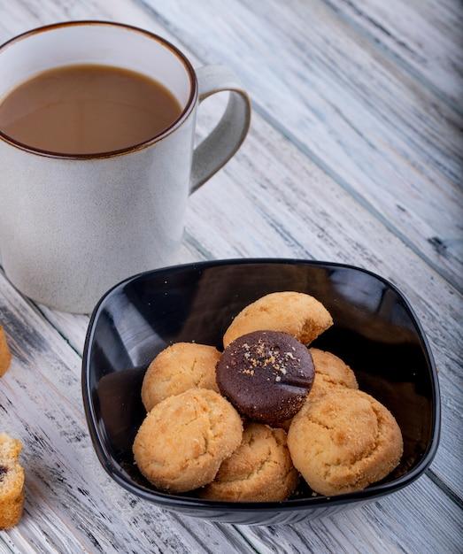 Vista lateral de biscoitos em uma tigela preta e um copo com cacau Foto gratuita