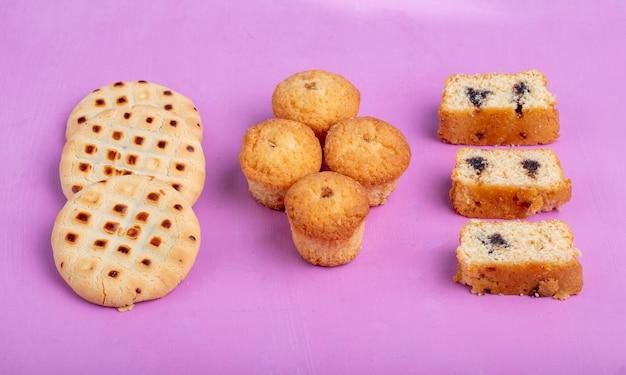 Vista lateral de bolos e bolos e biscoitos em roxo Foto gratuita