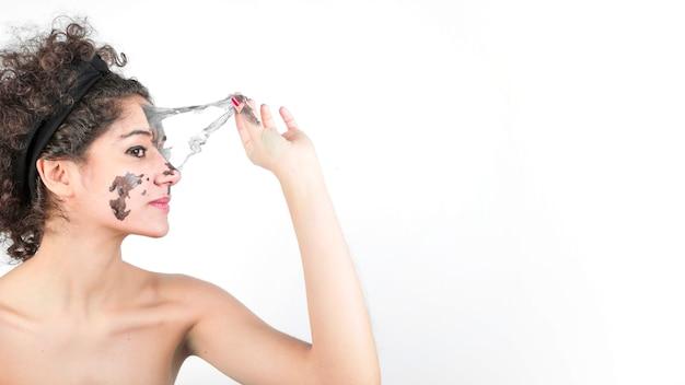Vista lateral, de, bonito, mulher jovem, removendo, pretas, máscara facial Foto gratuita