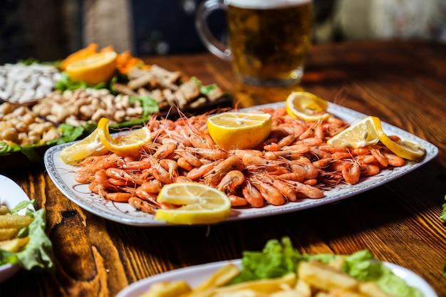 Vista lateral de camarão cozido com fatias de limão em um prato com lanches de cerveja e um copo de cerveja na mesa Foto gratuita