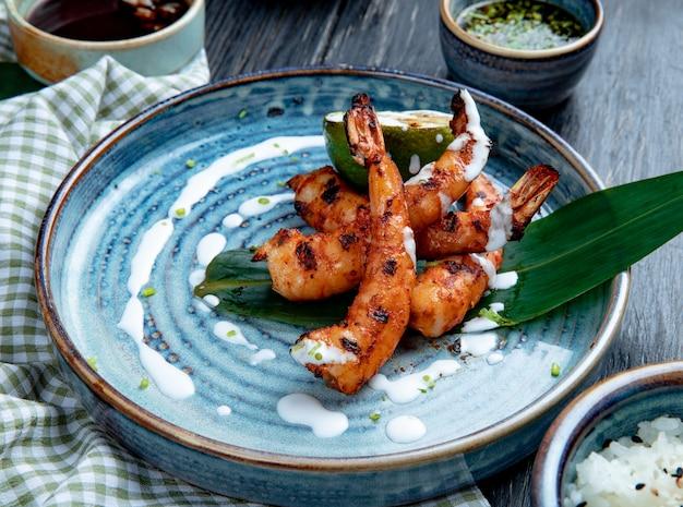 Vista lateral de camarão grelhado com molho num prato de madeira Foto gratuita