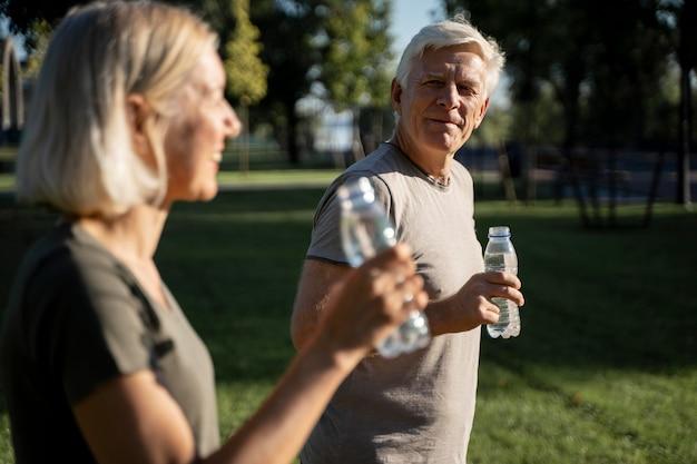 Vista lateral de casal bebendo água ao ar livre Foto gratuita